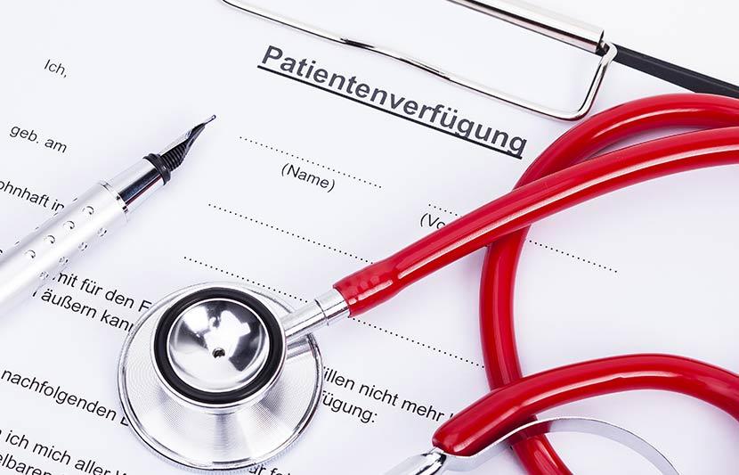 Ein Formular für eine Patientenverfügung, auf dem ein Kugelschreiber und ein Stethoskop liegen.