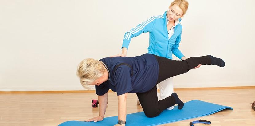 ältere Dame macht Rückengymnastik wegen eines Bandscheibenvorfalls