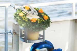 Seeurne mit Blumenschmuck bei Seebestattung an Bord eines Schiffes.