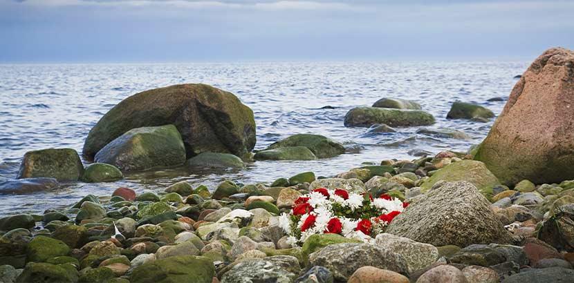Blumenkranz, der nach einer Seebestattung an den Strand gespült wurde.