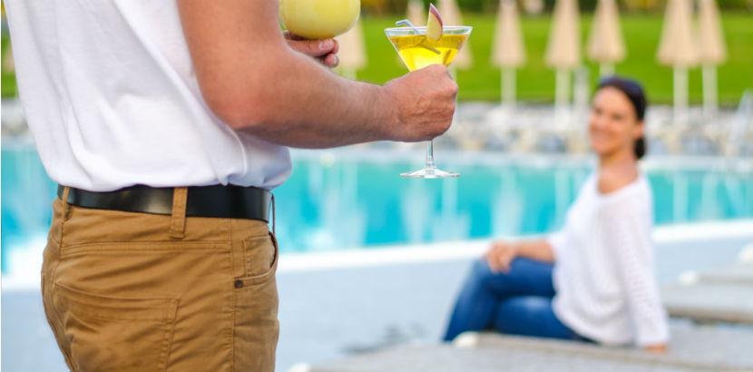 Single Hotels Österreich: Mann bringt Cocktails zu einer Frau am Pool.