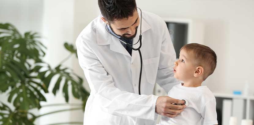 Junger Arzt, der das Herz eines kleinen Jungen abhört. Kinderkardiologe Wien.