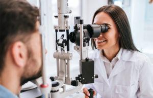 Eine Augenärztin, die durch ein Gerät hindurch in das Auge eines Patienten schaut.
