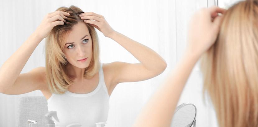 Junge Frau, die vor dem Spiegel eine blonde Echthaarperücke anlegt. Echthaarperücken Wien.