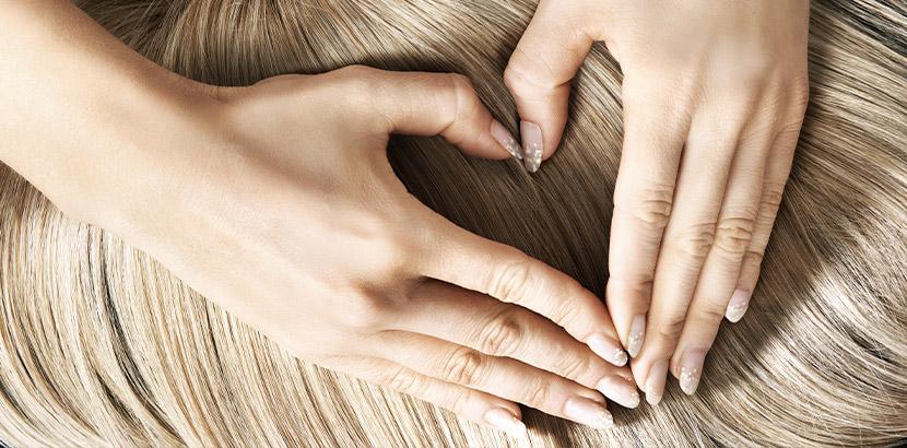 Zwei Frauenhände, die auf einer blonden Echthaarperücke ein Herz formen. Echthaarperücken Wien.