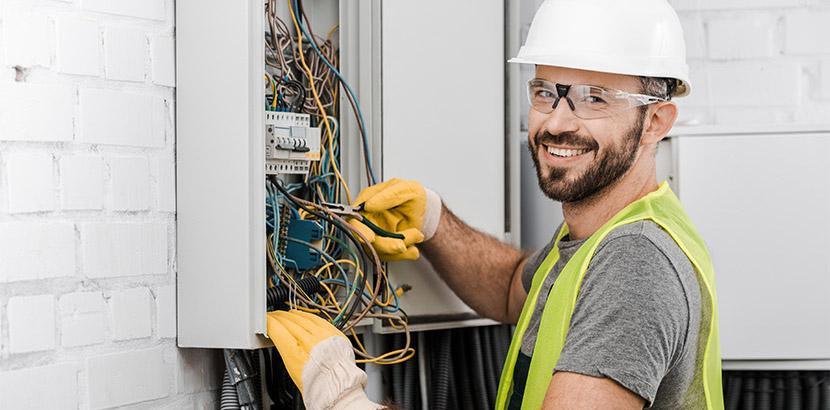 Hübscher lachender Elektriker, der an einer Kabelbox arbeitet. Elektriker Wien.