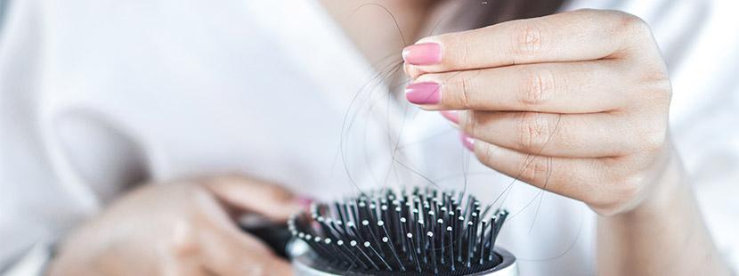 Nahaufnahme einer Frauenhand mit lackierten Fingernägeln, die tote Haare in der Hand hält. Endokrinologe Graz.