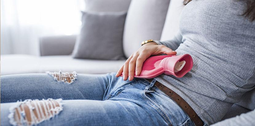 Frau, die auf dem Sofa sitzt und sich wegen Regelschmerzen eine Wärmflasche auf den Bauch drückt. Endometriose Symptome.