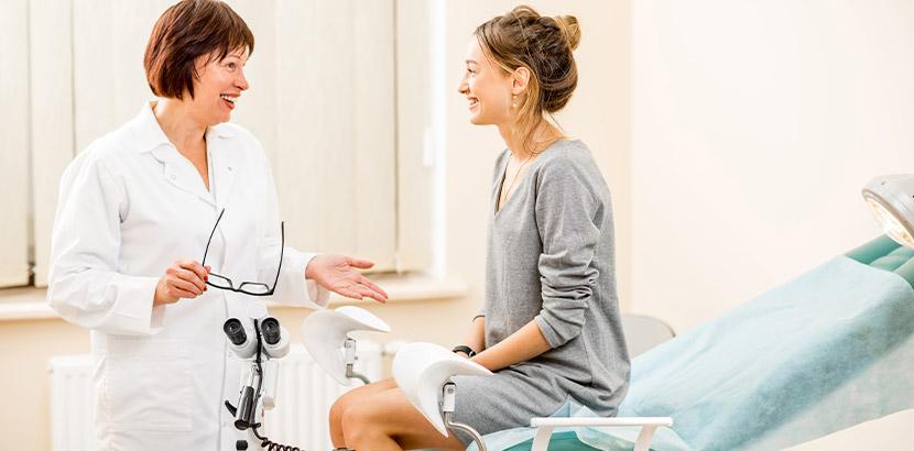 Junge hübsche Frau bei der Gynäkologin im Untersuchungsstuhl. Endometriose Symptome.