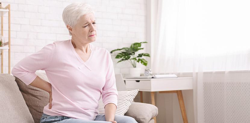 Ältere Frau, die auf dem Sofa sitzt und sich die schmerzenden Nieren hält. Inkontinenz bei Frauen.