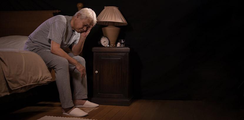 Ältere Frau, die unter Inkontinenz leidet und müde am Bettrand sitzt.