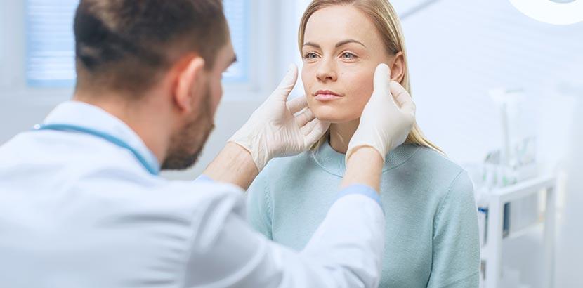 Lipofilling: Arzt untersucht Gesicht einer Frau