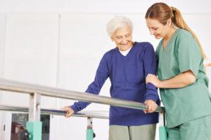 Junge blonde Physiotherapeutin mit einer älteren weißhaarigen Patientin in der Reha Maßnahme. Physiotherapie Linz.