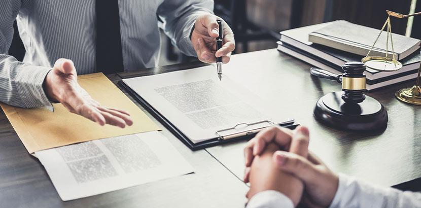 Ein Anwalt, der mit einem Klienten ein Dokument bespricht.