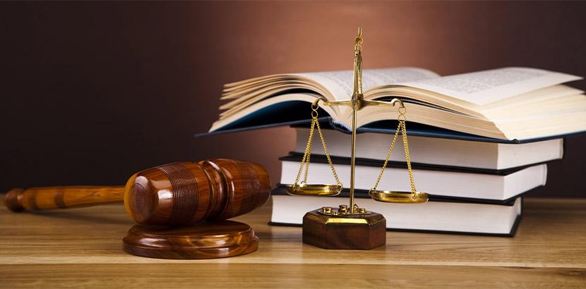 Ein Richterhammer, der neben einer Waage und Gesetzbüchern auf einem Tisch liegt.