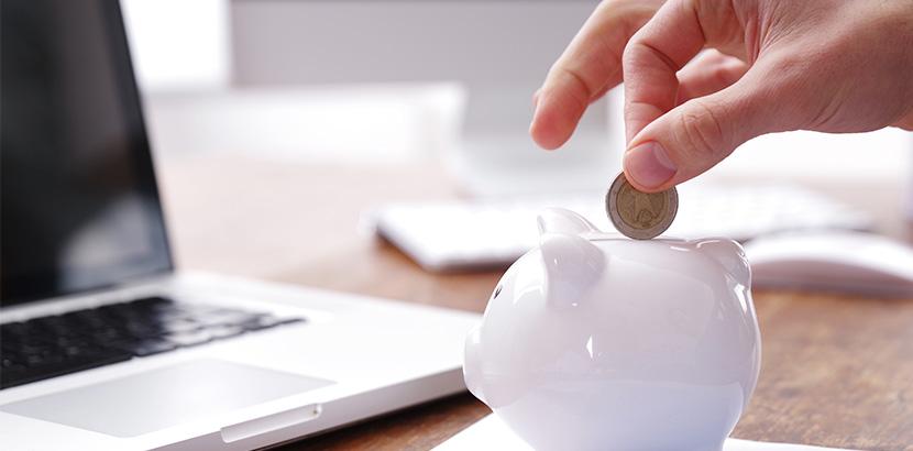 Eine Hand, die eine Münze in eine weißes Sparschwein fallen lässt. Privatkonkurs
