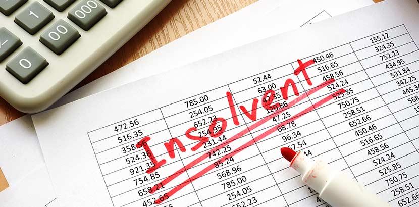 """Eine Tabelle voller Zahlen, über die mit rotem Stift das Wort """"insolvent"""" geschrieben wurde."""