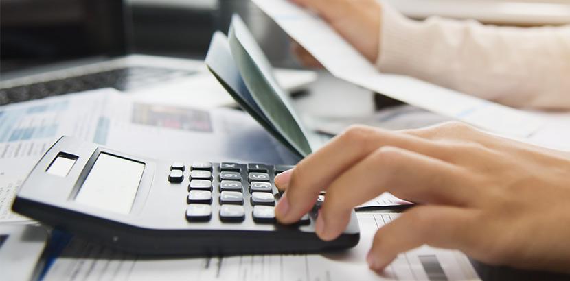 Eine Hand, die einen Taschenrechner auf einem Tisch voller Rechnungen bedient.