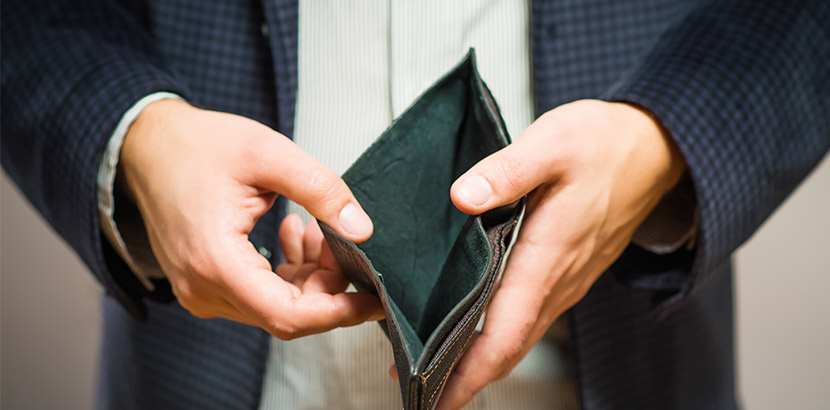 Ein Mann, der eine leere Geldbörse in Richtung der Kamera hält.