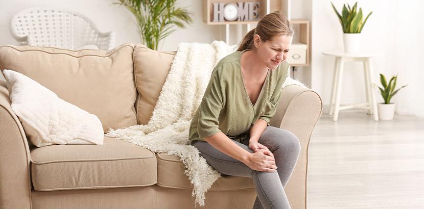 Junge Frau mit Schmerzen im Kniegelenk. Rheumatologe Wien.