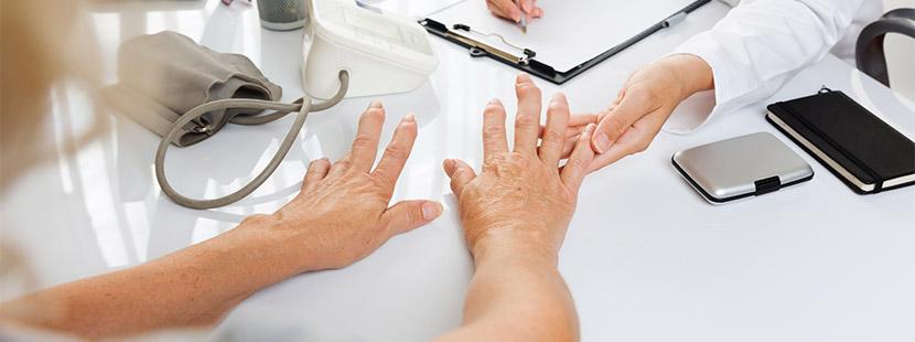 Ärztin, die die Hände einer Patientin untersucht, die von Rheuma geschwollen sind. Rheumatologe Wien.