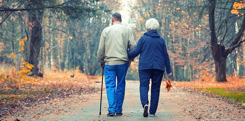 zwei ältere Menschen gehen spazieren um gegen eine PAVK vorzubeugen