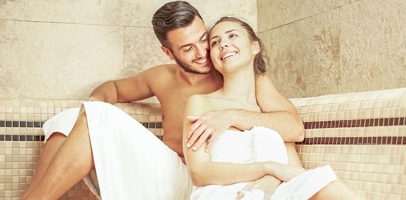 Ein Paar, das auf der Steinbank in einem Dampfbad sitzt. Wellnesshotel Tirol.