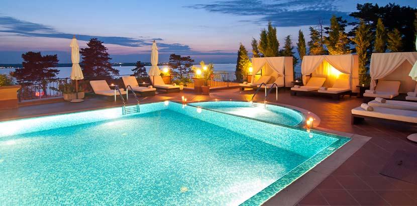 Ein Pool auf einer Terasse, der von Badeliegen umgeben ist. Wellnesshotel Tirol.