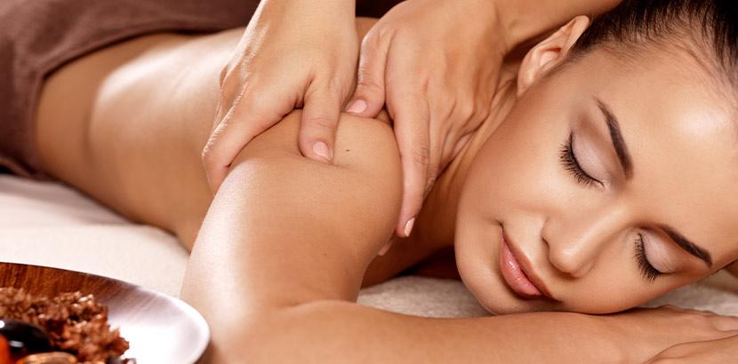 Eine Frau, die auf einem Handtuch liegt und deren Rücken massiert wird. Wellnesshotel Tirol.