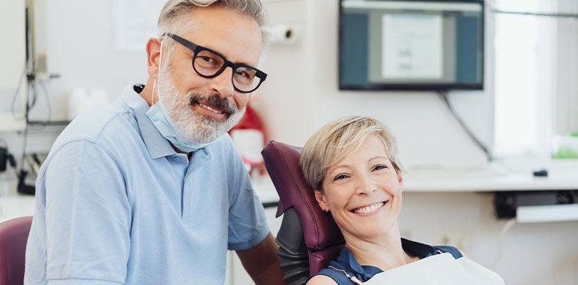 Ältere Patientin, die nach der Narkose beim Zahnarzt zufrieden und schmerzfrei aufwacht und in die Kamera lächelt.