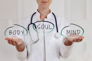Ärztin, die drei Sprechblasen in den Händen hält, in denen Mind, Body, Soul geschrieben steht. Steht für ganzheitliche Zahnmedizin Wien.