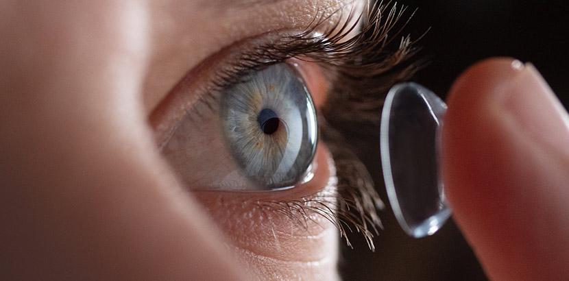 Eine Nahaufnahme eines Auges, auf das ein Finger eine Kontaktlinse auflegt.
