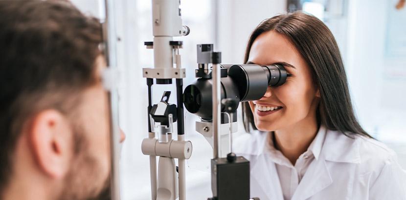 Eine Augenärztin, die eine Spaltlampe für eine Untersuchung verwendet. Augenarzt Salzburg