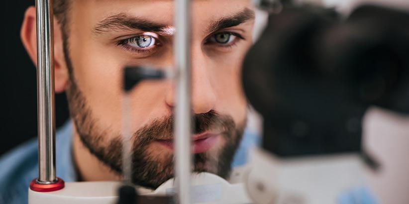 Ein Mann mit Bart, der im Rahmen einer Untersuchung in den Lichtpunkt einer Spaltlampe schaut.