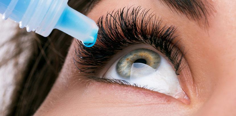 Eine Nahaufnahme von einem Auge, in das aus einer Flasche Augentropfen eingetropft werden.