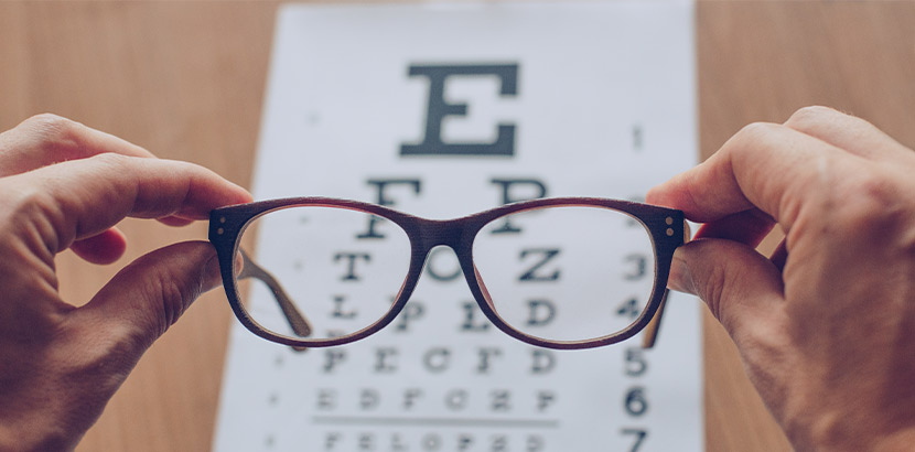 Zwei Hände, die eine braune Brille vor eine Sehtesttafel halten.