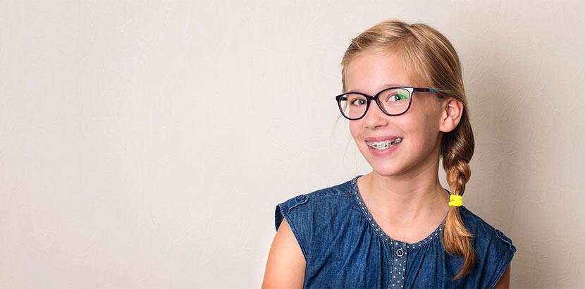 Süßes blondes Mädchen, das eine gratis Zahnspange trägt und in die Kamera lächelt.