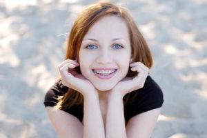 Hübsches junges Mädchen, das eine gratis Zahnspange trägt und in die Kamera lächelt.