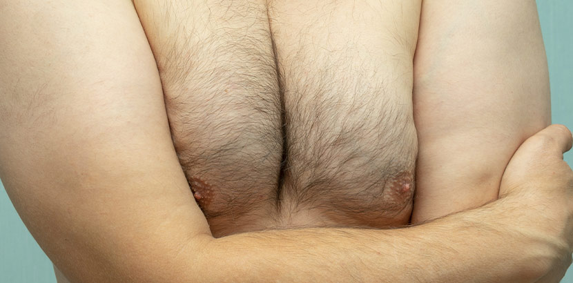 Ein Mann verschränkt vor seiner Brust die Arme.