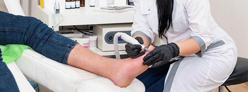 Hautärztin, die einen Patienten wegen Fußpilz behandelt. Hautarzt Graz.