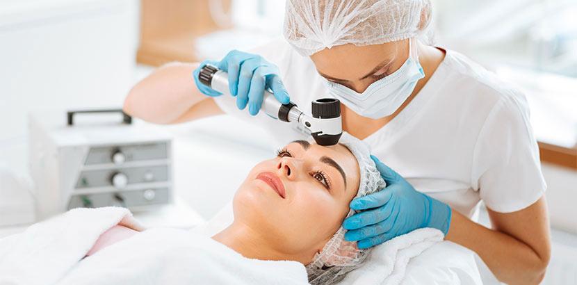 Hübsche junge Hautärztin, die eine dermatologische Untersuchung bei einer jungen brünetten Patientin macht. Hautarzt Graz.