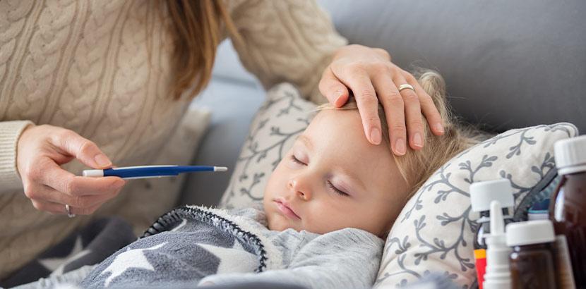 Eine Mutter, die ihrem kranken Kind die Hand auf die Stirn legt und einen Fieberthermometer hält. Kawasaki Syndrom