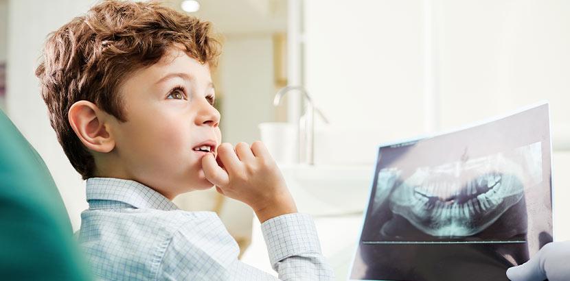 Kleiner Junge im Behandlungsstuhl beim Kieferorthopäden, der ihm ein Röntgenbild seiner Kiefer zeigt. Kieferorthopäde Wien.