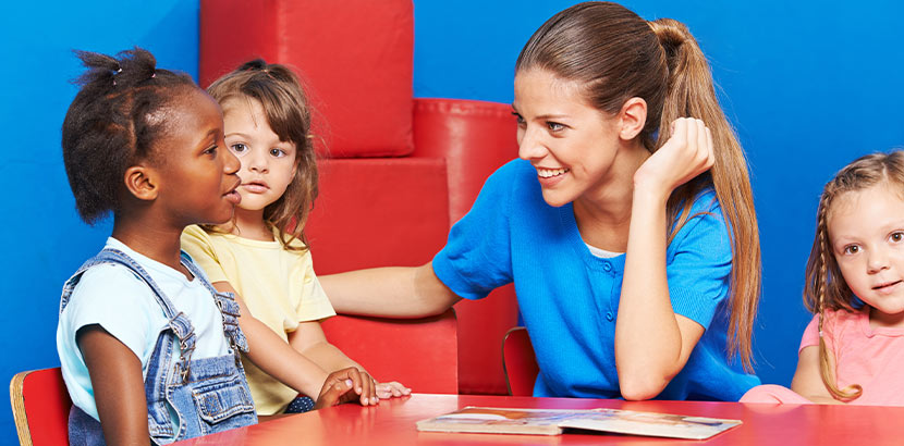 Junge blonde Logopädin bei der Arbeit mit einer Gruppe von Kindern. Logopäde Wien.