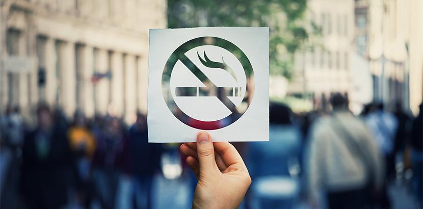 Ein Nichtraucher Schild vor einer belebten Straße voller Verkehr und Menschen.