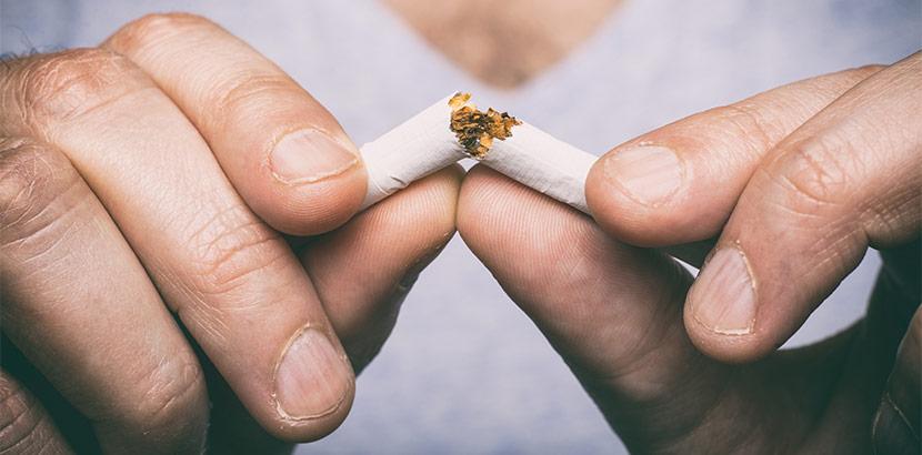 Zwei Hände, die eine Zigarette zerbrechen. Rauchen aufhören