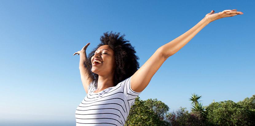 Eine Frau, die voller Freude ihre Arme in den Himmel streckt. Rauchen aufhören