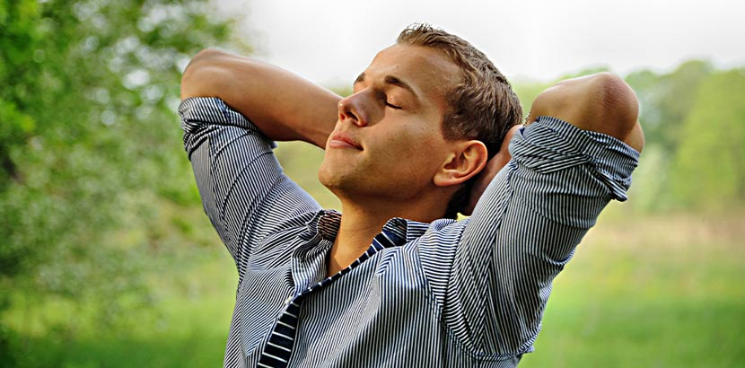Ein Nichtraucher, der mit geschlossenen Augen tief durchatmet. Rauchen aufhören