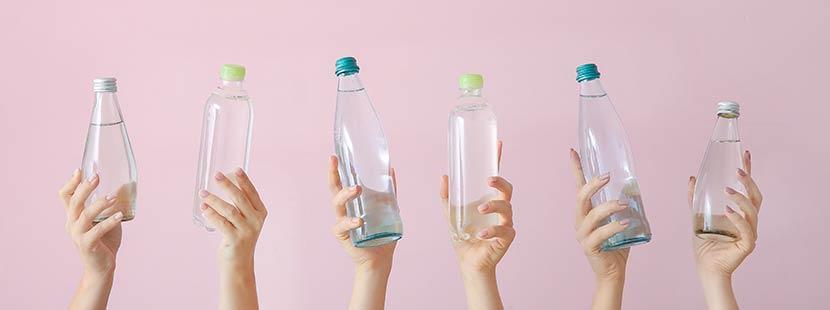 Hände, die Wasserflaschen hochhalten, vor rosa Hintergrund. Säure Basen Haushalt.