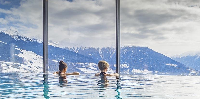 zwei Frauen in Pool mit Aussicht auf Berge in Salzburg